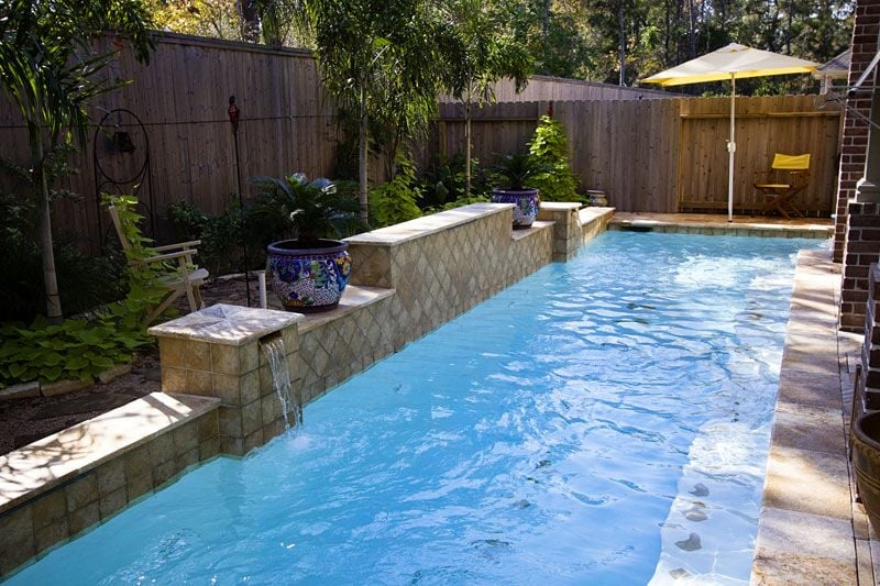 Narrow lap pool with swim jets and raised wall with for Narrow pools