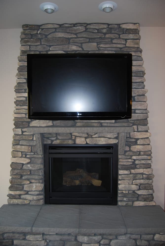 This Tv Was Mounted On A Stone Surface Above The Fireplace