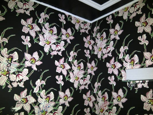 ... with pink floral wallpaper with black and white crown molding