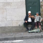 An elderly couple plays the violin and accordion next to the steps of Scare Coeur