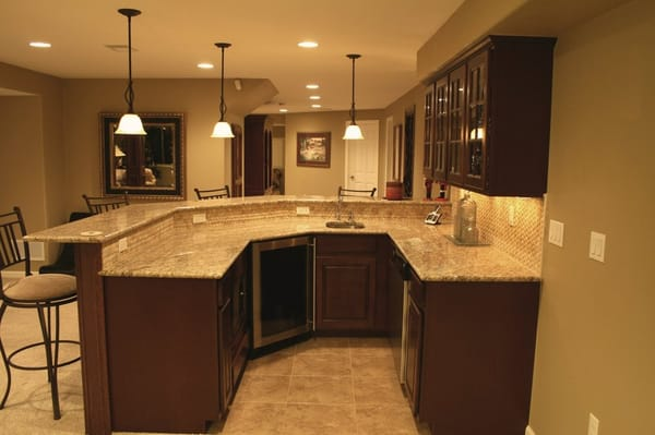 wet bar with granite counter, mosaic tile back splash in basement